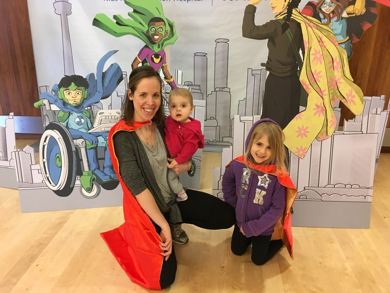 Mom and two kids posing in capes in front of a backdrop of spina bifida super heroes.