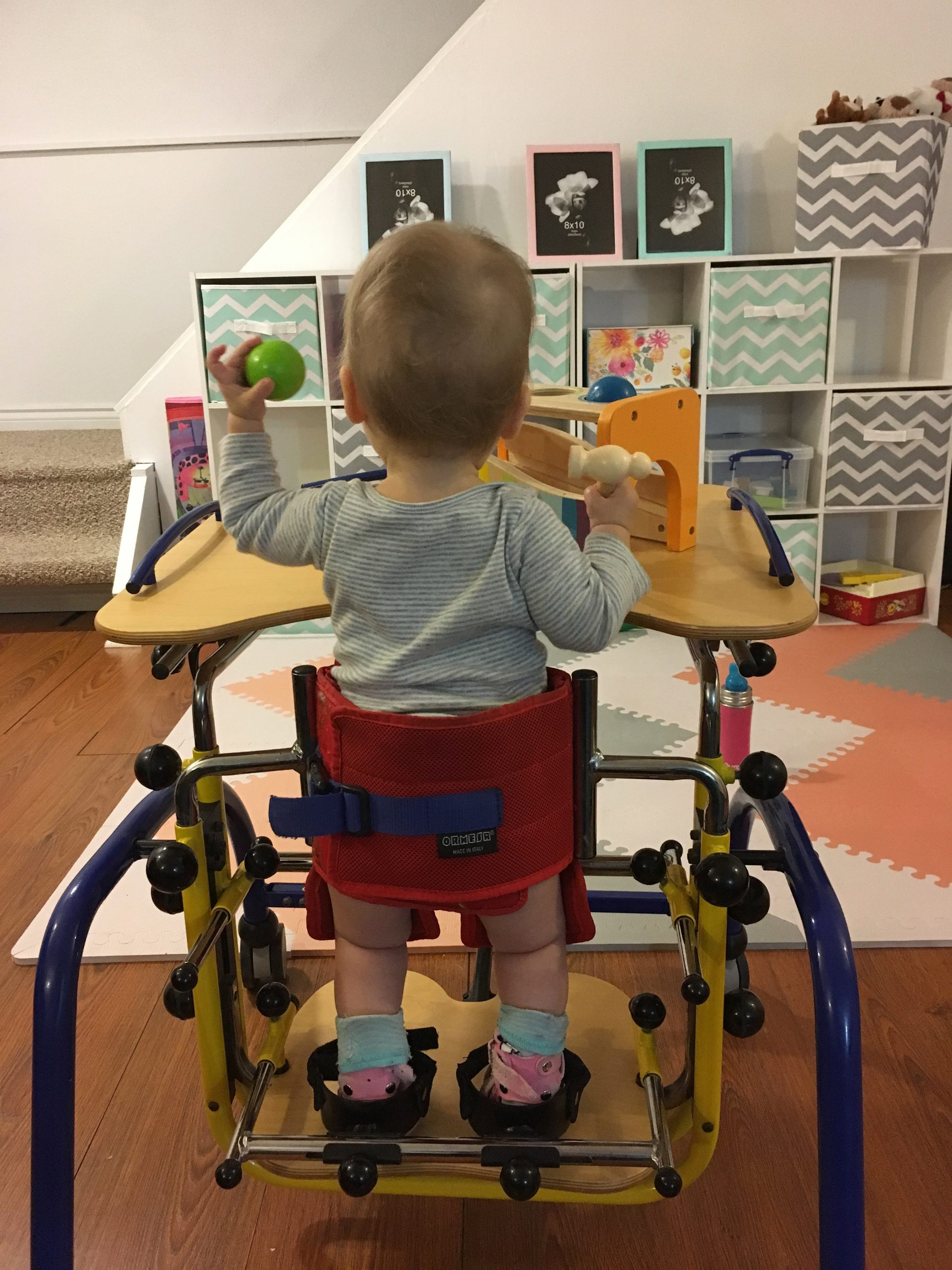 Child in a mobility device playing at a table.