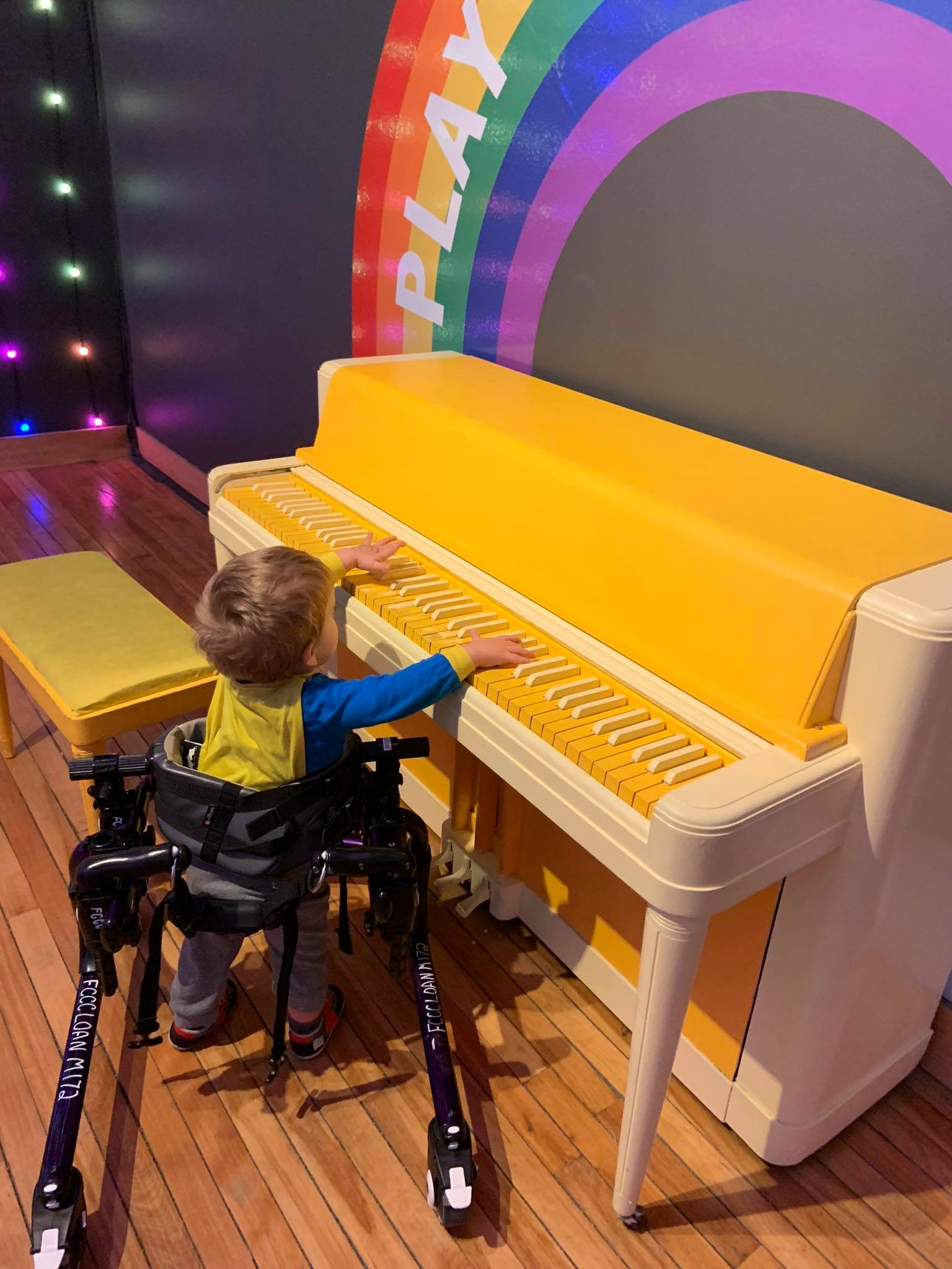 Child in a walker playing a piano.