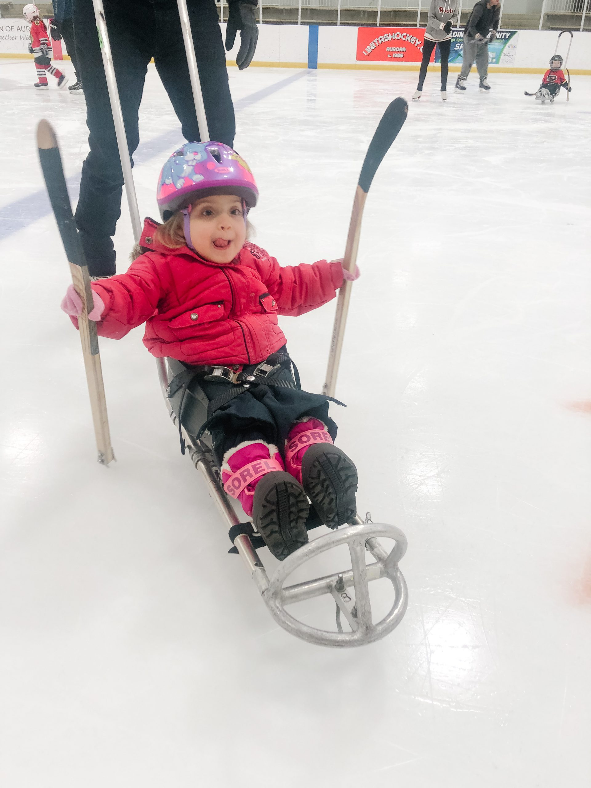 Child playing sledge hockey.